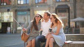 Groep Jongeren die Selfie nemen in openlucht Gebruikend Smartphone op het Stadsvierkant tijdens Sunny Summer Day Twee Meisjes en stock video