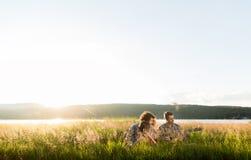 Groep jongeren in muziek van de zonsondergang de speelgitaar Stock Foto