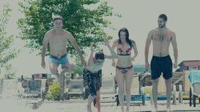 Groep jongeren op vakantie die in de pool springen stock video