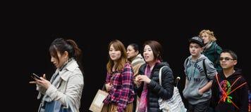 Groep jongeren tegen zwarte muur Stock Foto