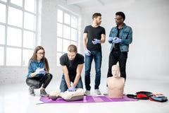 Groep jongeren tijdens de eerste hulp opleiding stock afbeelding