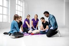 Groep jongeren tijdens de medische eerste hulpcursussen binnen stock fotografie