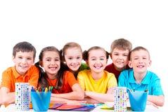 Groep kinderen die bij een lijst zitten Stock Foto