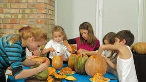 Groep Kinderen die Halloween-Pompoenen snijden stock video