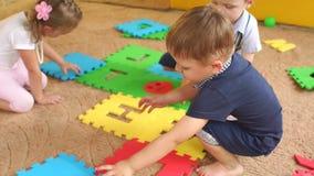 Groep kinderen die met een groot zacht raadsel spelen stock videobeelden
