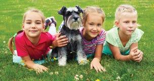 Groep kinderen die op groen gras in de lentepark spelen Stock Foto's