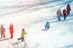 Groep kinderen die op sneeuw in de wintertijd spelen stock foto