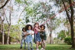 Groep kinderen die touwtrekwedstrijd spelen bij het park stock afbeeldingen