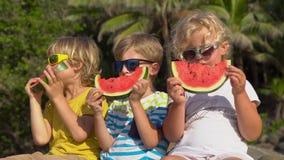 Groep kinderen die watermeloenzitting op een tropisch strand eten Kinderjarenconcept Het concept van de zomer stock footage