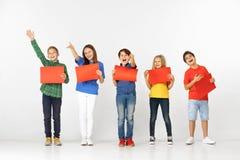 Groep kinderen met rode die banners in wit worden geïsoleerd royalty-vrije stock foto