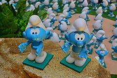 Groep kleine blauwe smurfs die en op rotsachtige oppervlakte welkom heten goedkeuren stock afbeeldingen
