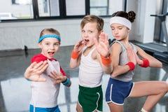 Groep kleine jonge geitjes in sportkleding die en bij camera in gymnastiek uitoefenen stellen stock foto