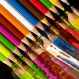 Groep kleurpotloden in het water wordt weerspiegeld dat stock fotografie