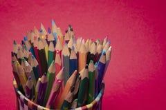 groep kleurrijke potloden op een roodachtige geweven achtergrond royalty-vrije stock foto's