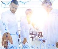 Groep laboratoriumwetenschappers die hun onderzoek naar bespreken royalty-vrije stock afbeeldingen