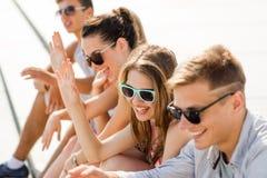 Groep lachende vrienden die op stadsvierkant zitten Stock Foto's