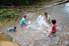 Groep landelijke kinderen die in water samen spelen stock foto