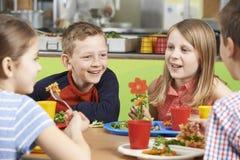 Groep Leerlingen die bij Lijst in Schoolcafetaria zitten die Lunc eten stock afbeelding