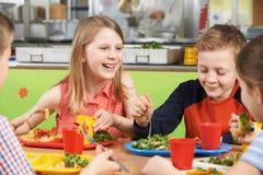 Groep Leerlingen die bij Lijst in Schoolcafetaria zitten die Lunc eten royalty-vrije stock fotografie