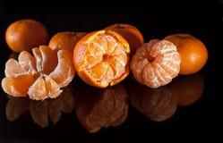 Groep mandarins met bezinning over zwarte achtergrond Stock Fotografie