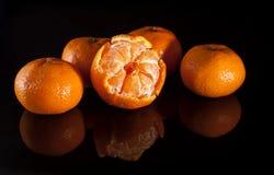Groep mandarins met bezinning over zwarte achtergrond Stock Foto's