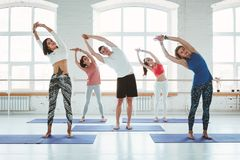 Groep mannen en vrouwen die en geschiktheid opleiding in klasse opwarmen doen De jonge actieve mensen doen samen yoga royalty-vrije stock afbeelding