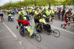 Group of marathon runners pushing running wheel chairs with disabled persons helping them fulfill the run.