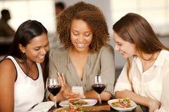Groep meisjes die een smartphone bekijken Stock Foto's