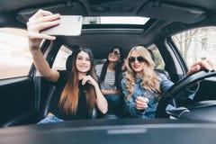 Groep meisjes die pret in de auto hebben en selfies met camera nemen stock afbeeldingen