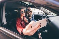 Groep meisjes die pret met de auto hebben Het nemen selfie terwijl het drijven in reis stock afbeelding