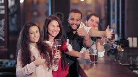 Groep meisjes en jongens bij de bar met een bier stock video