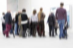 Groep mensen binnen een onscherpe tentoonstellingszaal, stock foto's