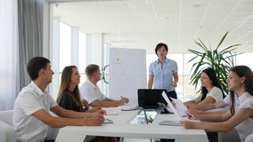 Groep mensen in bureaukleren bij bureau en mentor dichtbij Whiteboard in Commercieel centrum stock video