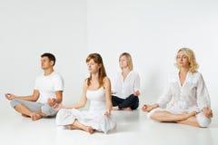 Groep mensen die en yoga in wit ontspannen doen Royalty-vrije Stock Afbeeldingen