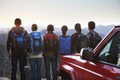 Groep mensen die zich naast de auto bevinden en de bergen bekijken stock foto