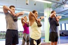 Groep mensen met kettlebells die in gymnastiek uitoefenen Stock Fotografie