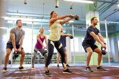 Groep mensen met kettlebells die in gymnastiek uitoefenen Stock Afbeelding