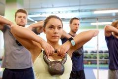 Groep mensen met kettlebells die in gymnastiek uitoefenen Royalty-vrije Stock Foto
