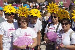 Groep mensen met zon op hun hoofd en roze ventilator Stock Afbeeldingen