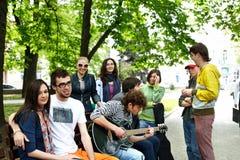 Groep mensen op bank in park. Royalty-vrije Stock Afbeeldingen