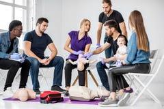 Groep mensen tijdens de eerste hulp opleiding stock afbeelding
