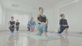 Groep midden oude vrouwen die hun organismen stemmen tijdens een zitting van de yogaklasse in een geschiktheidsstudio - stock footage