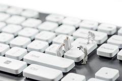 Groep miniatuurcriminalists die computertoetsenbord inspecteren Cybercrimeconcept Stock Fotografie
