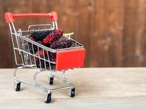 Groep moerbeibomen in rood boodschappenwagentje op houten lijst De moerbeiboom dit een fruit en kan worden gegeten in heeft een r stock foto's