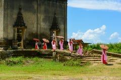 Groep Mon-nonnen die naar aan geruïneerde Boeddhistische kerk lopen stock afbeelding