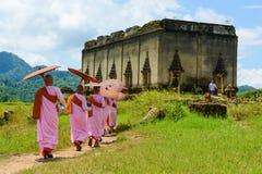 Groep Mon-nonnen die naar aan geruïneerde Boeddhistische kerk lopen royalty-vrije stock fotografie