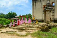 Groep Mon-nonnen die van geruïneerde Boeddhistische kerk opstappen royalty-vrije stock afbeeldingen