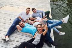 Groep mooie jongeren die Selfies liggend op de pijler, de beste vrienden van meisjes en jongens met genoegen doen Royalty-vrije Stock Fotografie