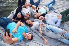 Groep mooie jongeren die Selfies liggend op de pijler, de beste vrienden van meisjes en jongens met genoegen doen Royalty-vrije Stock Afbeelding