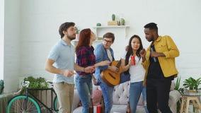 Groep multi etnische vrienden die en gitaar dansen spelen terwijl huispartij hebben stock videobeelden